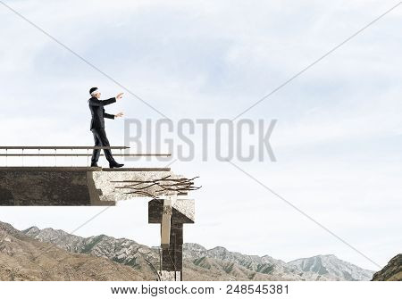 Businessman Walking Blindfolded On Concrete Bridge With Huge Gap As Symbol Of Hidden Threats And Ris