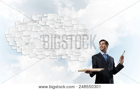 Conceptual image of young and successful businessman in black suit holding paintbrush in hand and smiling while standing with chatting cloud against cloudy skyscape on background. poster