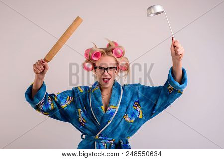 Angry Housewife In A Dressing Gown And Curlers With A Ladle In Her Hand.