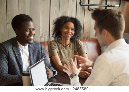 Caucasian Architect Talking To Smiling African American Couple, Explaining Housing Project Idea In C
