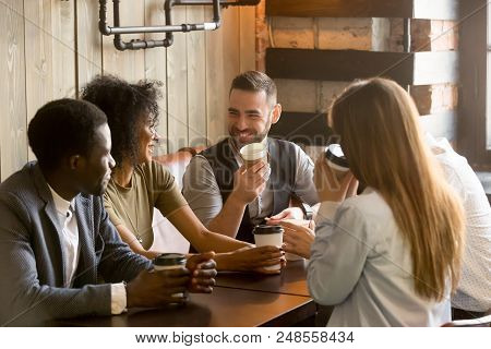 Smiling Multiracial People Enjoying Coffee, Talking Spending Pleasant Time Together In Cozy Coffee S