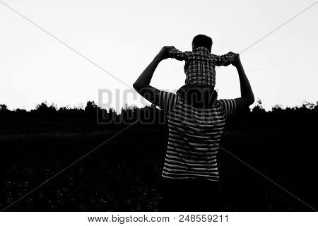 Father And Son Playing In Field At Sunset, Having Quality Family Time Together Silhouette.