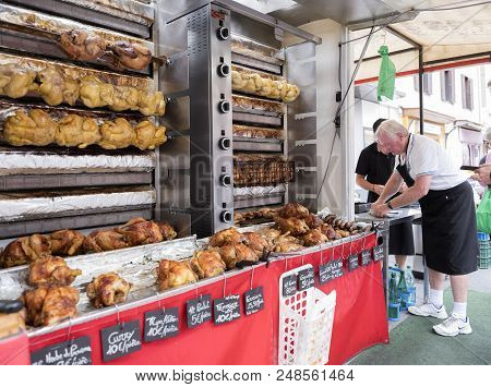 Besancon, France, 10 June 2018: Vendor Sells Golden Brown Chickens On Grill On Market In French Town