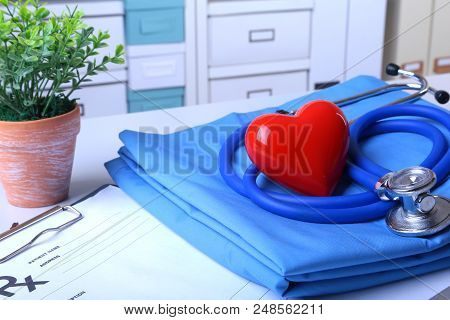 A Medical Stethoscope With Red Heart And Rx Prescription Are Lying On A Medical Uniform.