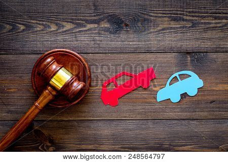 Car Accident Lawsuit Concept. Two Collided Cars Near Judge Gavel On Dark Wooden Background Top View.