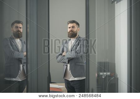 Confidence And Success Concept. Bearded Man Look Out Room Door. Businessman In Modern Office With Gl