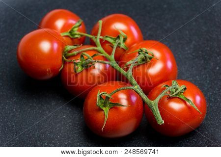 Close-up Of Red Cherry Tomatoes On A Black Plate. View From Above To Fresh Cocktail Tomatoes On A Bl