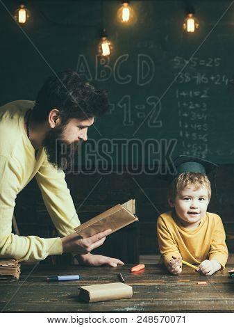 Reading Concept. Man Teacher Reading Book To School Boy. English Reading And Grammar. Reading Feeds