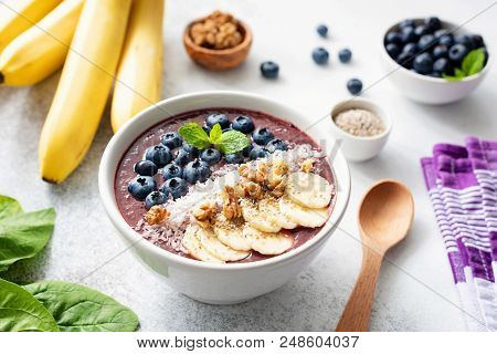 Acai Smoothie Bowl With Superfood Toppings On Concrete Background. Purple Smoothie In White Bowl Wit