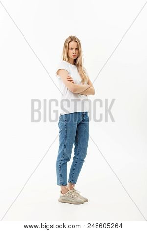 Serious Confident Young Woman With Long Blond Hair Dressed In Casual Wear Standing Looking At The Ca