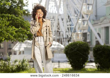 Lively Conversation. Gorgeous Curly Woman In A Stylish Outfit Standing In A Little Park And Having A