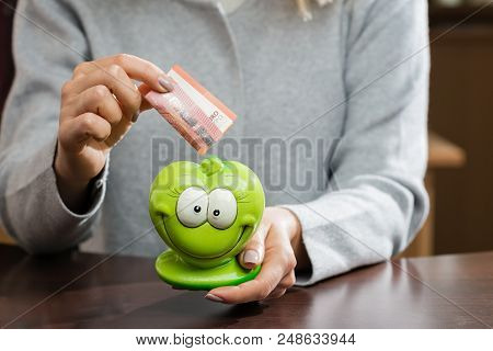 Woman Putting Business Card In A Funny Green Moneybox. Concept Of Future, Business, Saving Money, Ec