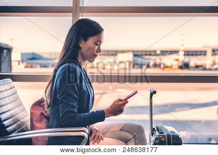 Airport phone travel Asian businesswoman using mobile smartphone in business class lounge waiting for plane flight texting sms message. Technology and travel people VIP lifestyle.