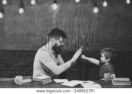 Father And Son. Handsome Teacher And Cute Kid Playing In Classroom. Schoolboy Achieving The Task. Li