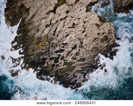 Aerial above coastline rocks with stormy seas