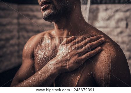 Young Afro-american Man Taking Shower In Bathroom At Morning. Standing Man With Bare Torso In Bathro