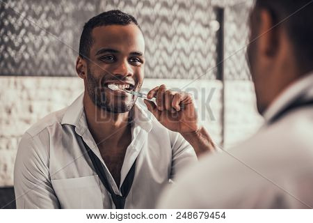 Afro American Man Cleaning Teeth In Bathroom At Morning. Standing Man In Shirt In Bathroom. Personal