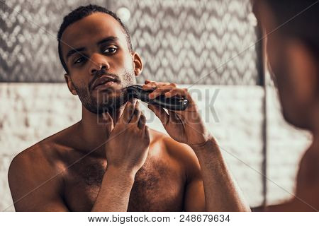 Young Afro American Man Shaving In Bathroom At Morning. Standing Man With Bare Torso In Bathroom. Pe