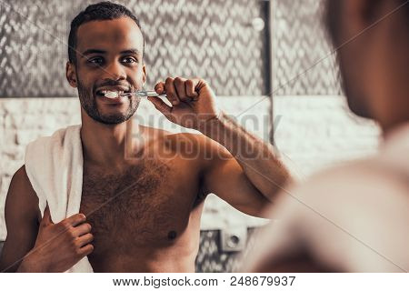 Afro American Man Cleaning Teeth In Bathroom At Morning. Standing Man With Bare Torso In Bathroom. P