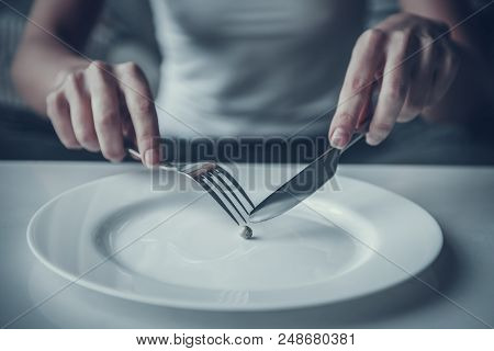 Close Up. Woman Eating One Pea With Fork And Knife. Diet Concept. Weight Loss Problem. Starving Youn