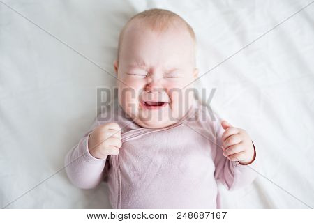Cute Little Baby Girl Crying On The Bed