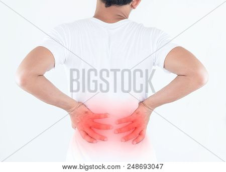 Portrait Of Young Man Touching Him Back With Pained Expression, Suffering From Backache After Long W