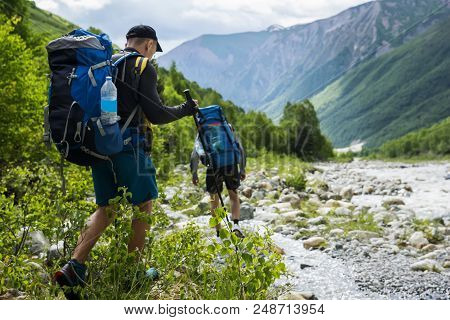 Group Of Hikers Walking In Mountains. Tourists With Hiking Backpacks On Beautiful Mountain Landscape