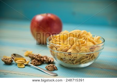 Tasty Cornflakes Wit Walnut And Apple In Glass Bowl On Blue Background. Corn Flakes. Healthy Breakfa