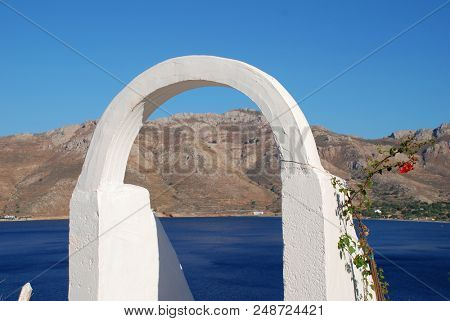 A white archway frames Livadia harbour on the Greek island of Tilos.