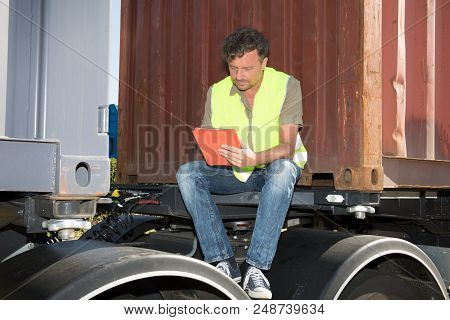 Truck Driver With Tablet Sit Outdoor In A Trailer