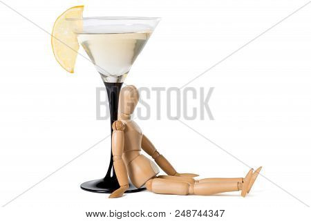 Wooden Mannikin Sitting Near Glass Of Vermouth. Concept Of Drunkenness, Alcohol Abuse. Isolated On W