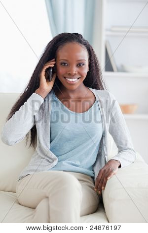 Close up of smiling woman with her mobile phone on the sofa