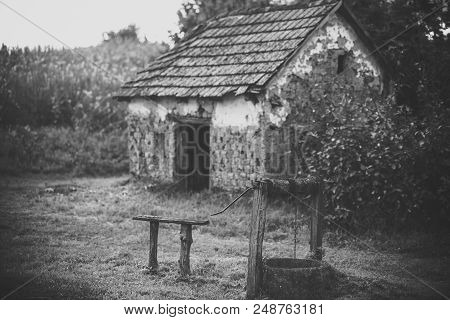 Abandoned house. House barrack with old well in yard. Rural lifestyle, countryside. Decay, decline, ruins. Architecture, structure, construction Village with abandoned building vintage filter poster