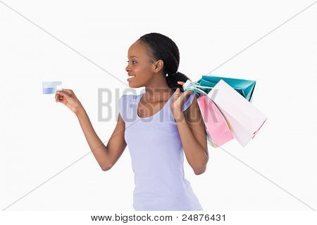 Uśmiechający się z jej zakupy i karty kredytowej na białym tle