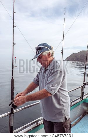 Retired Senior Male Adult Tourist On A Fishing Charter Boat Looking At Rod, At Mangonui, Far North D