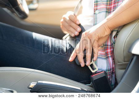 Closeup Woman Hand Sitting Inside Car Fastening Seat Belt. Safety Belt Safety First.