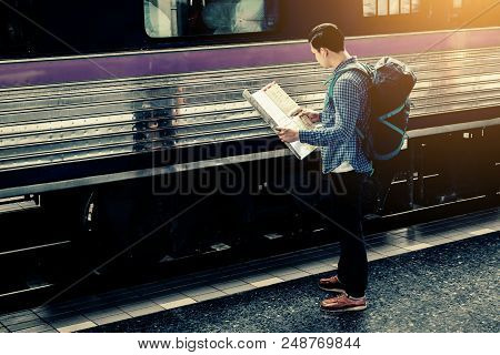 Young Asian Man Holding Map Paper And Looking Route With Plan For Travel.