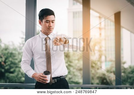Confident Asian Man Standing Checking Time And Holding Coffee Cup With Looking At Watches At Outside
