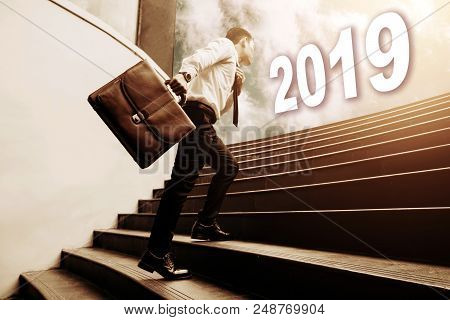Businessman Holding Briefcase And Walking On Staircase And Looking To Future 2019 Newyear Concept.