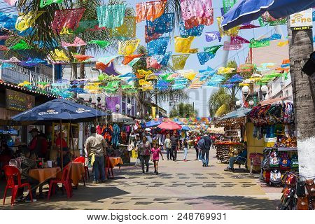 Tijuana, Baja California/mexico - June 20, 2018:  People Shop And Walk Below Colorful Hanging Flags