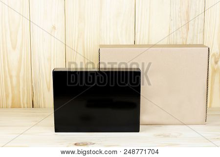 Blank Black Box And Blank Brown Box On Wooden Table.zoom In.