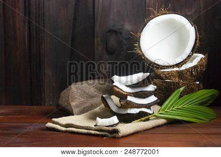 Coconut Half And Coconut Pieces And Leaf  On Wooden Table And Black Wooden Background.