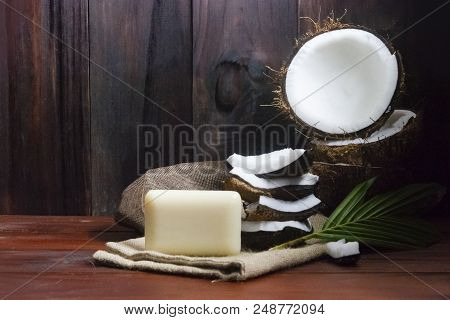 Coconut Soap With Coconut Half And Coconut Pieces And Leaf On Wooden Table.