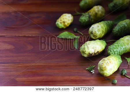 Noni Fruit And Leaves On Red And Brown Wooden Right Corner.