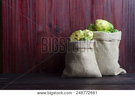 Noni In Sack  On Wooden Table And Wooden Background