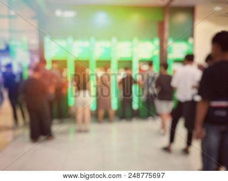 Blurred Abstract Background Of People Standing And Queuing, Waiting Up A Queue Or Line Up To Withdra