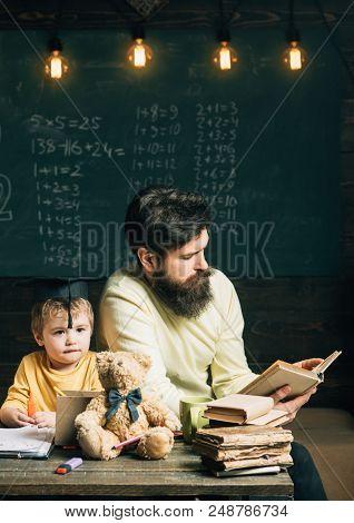Reading Concept. Teacher Reading Book To School Boy. Little Child Listen To Man Reading Book In Clas