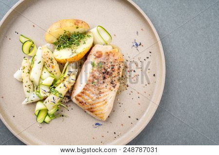 Modern German fried cod fish filet with white asparagus tips and roast potatoes as top view on a plate with copy space right