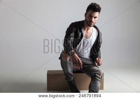 sexy man wearing leather jacket and grey jeans sitting on a wooden crate on light grey background