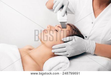 Beautiful woman receiving ultrasound cavitation facial peeling. Cosmetology and facial skin care poster